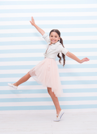 Child concept. Happy little child dancing. Child girl smile in fashion dress. Child and childhood. sense of freedom