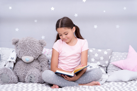 Read before sleep. Girl child sit bed with teddy bear read book. Kid prepare to go to bed. Pleasant time in cozy bedroom. Girl kid long hair cute pajamas relax and read book to bear toy