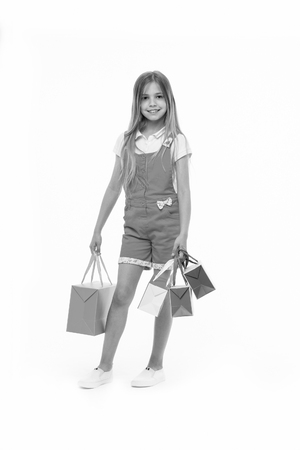Little girl with shopping bags isolated on white. Child smile with paper bags. Happy kid shopper in fashion jumpsuit. Holidays preparation and celebration. After day shopping. sale and black friday Stock Photo