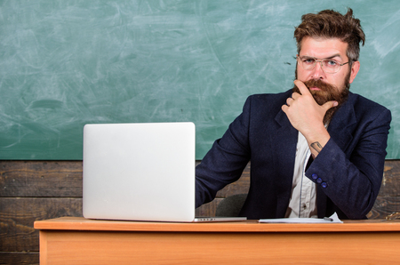 I am your new teacher. Teacher bearded hipster with eyeglasses sit in classroom chalkboard background. School teacher ready to start lesson. Teacher sit at desk with laptop. Back to school concept.