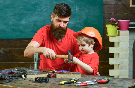 Father with beard teaching little son to use tools, hammering, chalkboard on background. Boy, child busy in protective helmet learning to use hammer with dad. Fatherhood concept.