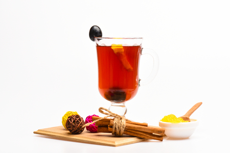 Seasonal beverage concept. Glass with mulled wine or hot drink with grape, cinnamon and honey on white background, close up. Glass with mulled wine with grape and cinnamon. Stock Photo