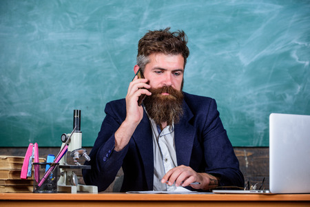 In touch with school. School principal or teacher calling parents to report about exam results. Man with beard talk phone classroom background. School teacher cares about communication with parents.