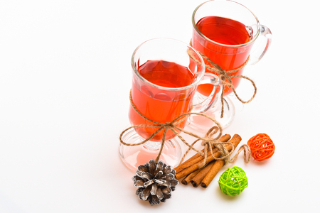 Glasses with mulled wine or cider tied with twine string on white background. Traditional mulled wine with spices. Mulled wine or hot beverage in glasses and cinnamon sticks. Hot drinks concept. Stock Photo