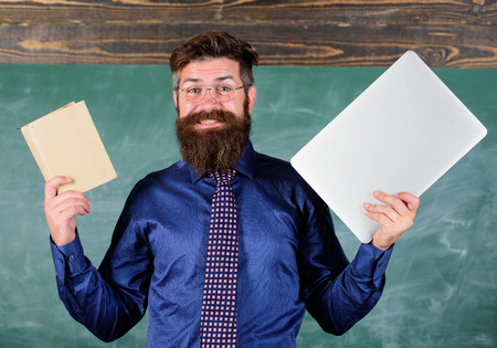 Teacher bearded hipster holds book and laptop. What would you prefer. Digital against paper. Teacher choosing modern teaching approach. Paper book against laptop. Choose right teaching method.
