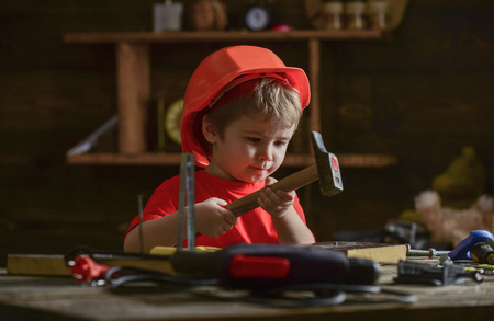 Child in helmet cute playing as builder or repairer, repairing or handcrafting. Toddler on busy face plays at home in workshop. Kid boy hammering nail into wooden board. Handcrafting concept. Archivio Fotografico
