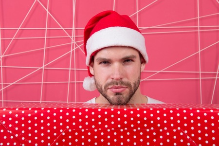 Santa bring gift for you. Man attractive santa claus carry big box. Ready to unpack your gift. Christmas holiday celebration. Man handsome unshaven santa hat hold gift box. Christmas gift concept.