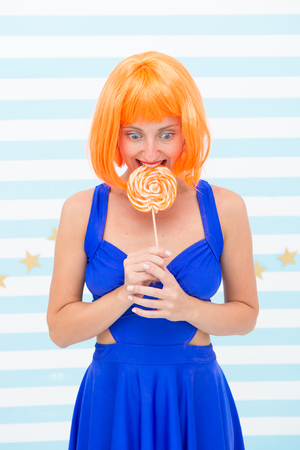 Crazy girl in playful mood. happy pinup model with lollipop in hand. Fashion girl with orange hair having fun. Cool girl with lollipop. Sexy woman. So much fun. Crazy party girl. Fun time.