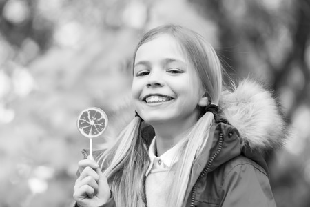 Girl smile with lollipop on natural background. Child smiling with candy on stick outdoor. Happy childhood concept. Food, dessert, snack. Punchy pastel trend Banque d'images