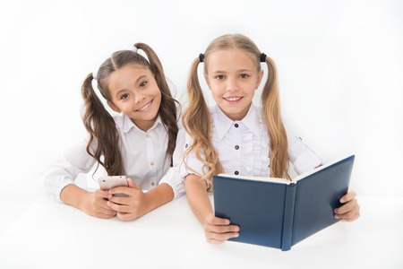 Getting information. Modern data storage instead big paper book. Little girls read paper book and ebook smartphone. Application for education. Educational application mobile phone. Education online. Stockfoto