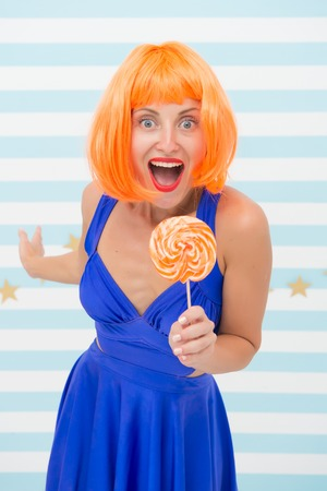 happy pinup model with lollipop in hand. Fashion girl with orange hair having fun. Cool girl with lollipop. Sexy woman. Crazy girl in playful mood. Sweet look. So much fun. Going crazy. Enjoy party. Banco de Imagens
