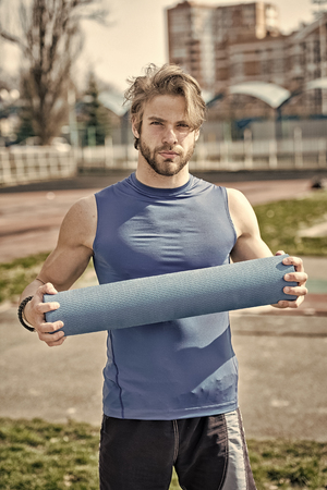 yoga. muscular man holding yoga or fitness mat for exercise in outdoor gym or arena in sportswear