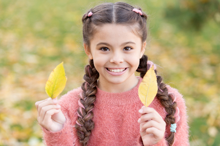Small child with autumn leaves. Happy little girl in autumn forest. Happy childhood. School time. Autumn leaves and nature. Trendy beauty. Feeling comfortable. Time to rest. In love with nature.