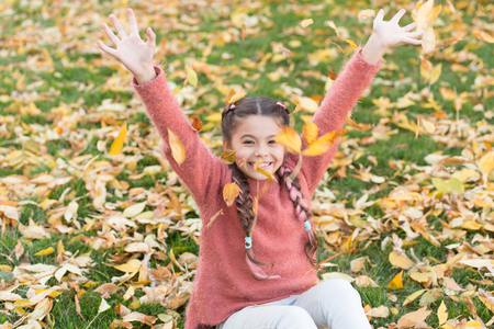 Small child with autumn leaves. Autumn leaves and nature. Happy little girl in autumn forest. Happy childhood. School time. Happy to be around. Enjoying autumn day. In love with nature.