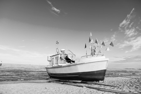 Boat on sand beach in Gdansk, Poland. Small ship on sea shore on blue sky. Vessel and water transport. Summer vacation and sea travel. Wanderlust