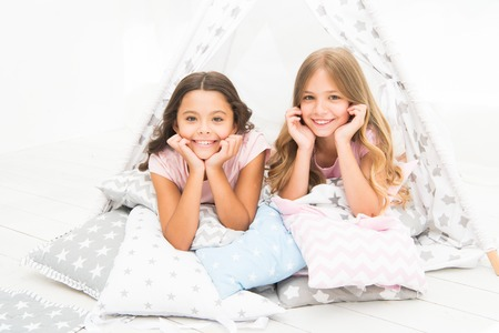Girls having fun tipi house. Girlish leisure. Sisters share gossips having fun at home. Pajamas party for kids. Cozy place tipi house. Sisters or best friends spend time together lay in tipi house.