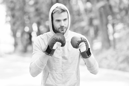 Training for big day. Man athlete on concentrated face with sport gloves practicing boxing punch, nature background. Boxer hood head practices jab punch. Sportsman boxer training with boxing gloves.