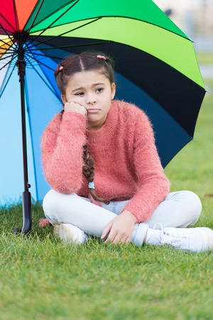 Ways brighten your fall mood. Colorful accessory for cheerful mood. Girl child long hair sad because of fall weather. Stay positive fall season. Little girl sad about fall while sit under umbrella.