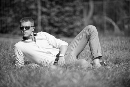 Businessman in sunglasses on sunny outdoor. Man relax on green grass. Handsome macho enjoy summer day. Fashion style and trend. Break time concept.
