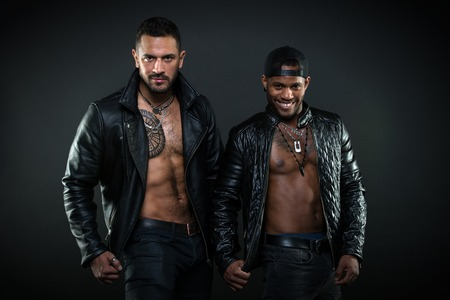 Bodybuilders with torsos. Cheerful African man with broad smile wearing cap. Brutal Caucasian man with tattoo on hairy chest. Bikers in leather jackets on muscular body, masculinity concept.