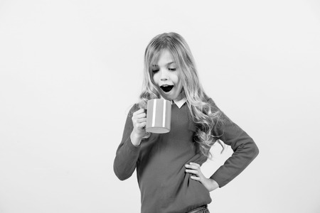 Health and healthy drink. Child with surprised face hold blue cup on orange background. Girl with long blond hair in red sweater with mug. Thirst, dehydration concept. Tea or coffee break.