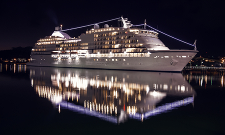 cruise ship at night, luxury cruises. Large luxury cruise ship on sea water at night with illuminated light docked at port of st.Johns, Antigua