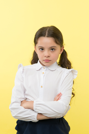 She does not agree with you. Girl serious face offended yellow background. Kid unhappy looks strictly. Girl school uniform folded arms on chest looks serious. Sensitive girl not want to talk. Foto de archivo