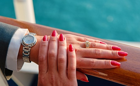 Female hands and wrist-watch with red manicure and golden ring on finger with diamonds near water, beautiful hands with watch. Archivio Fotografico