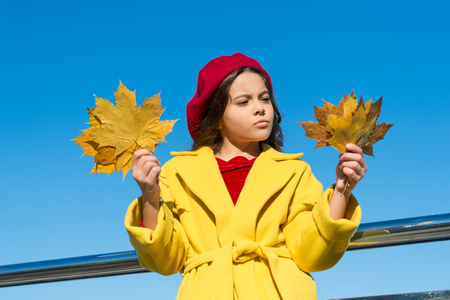 Little girl sad coming about autumn season. Tips for turning autumn into best season. Kid girl sad face hold maple leaves. Child with autumn maple leaves walk. Autumn coziness is just around.
