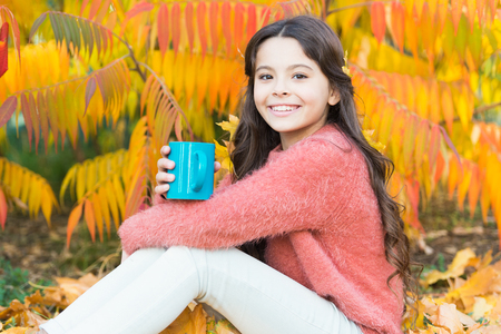 I have a wonderful childhood. Little child enjoy autumn hot drink. Little child relax at autumn tree. Happy childhood years. Lucky to play up in trees. Imagens