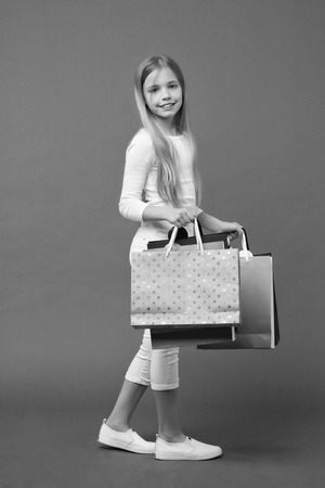 Happy kid carry shopping bags on violet background. Imagens