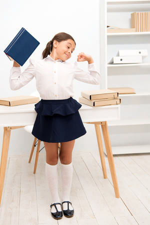 Girl child hold book while stretching white interior. Kid school uniform making exercise stretching increase productivity. Exercises to maintain vivacity. Role of active breaks in educational process. Imagens