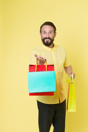 Offer bonus for client good idea. Man mature bearded cheerful face holds shopping bags. Man got unexpectable gifts. Guy surprised by gift yellow background. Presents make our lives more interesting. 版權商用圖片