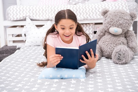 Enjoy favorite moment. Girl child lay bed with teddy bear read book. Kid prepare to go to bed. Girl kid long hair cute pajamas relax and read book to bear toy. Pleasant time in cozy bedroom.