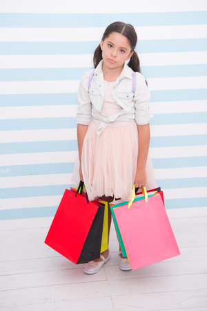 Shopping tiring exhausting activity. Child carries shopping bags striped background. Kid girl spend day buy things supplies for school. Back to school sales season. Girl exhausted holds bags. Stock fotó