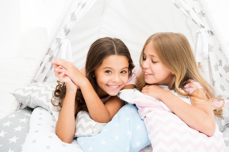 Sisters share gossips having fun at home. Pajamas party for kids. Cozy place tipi house. Sisters or best friends spend time together lay in tipi house. Girls having fun tipi house. Girlish leisure.