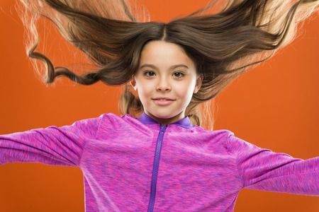 Kid girl long healthy shiny hair. Little girl grow long hair. Teaching child healthy hair care habits. Strong hair concept. Melanin substance give pigment. Person with brown has much more melanin. Foto de archivo