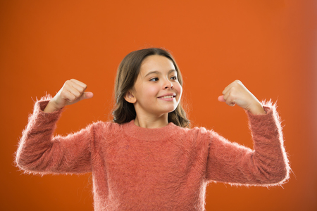Child cute girl show biceps gesture of power and strength.