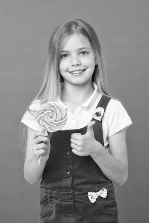 Girl eating big lollipop and shows thumb up. Sweet childhood concept.