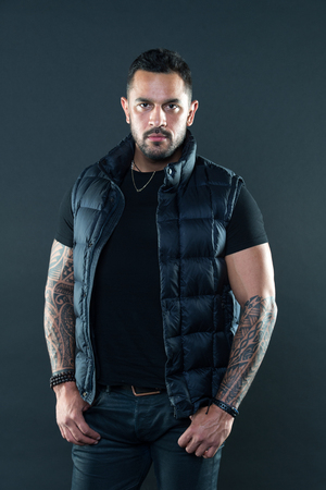 Bearded man posing with tattoos. Macho unshaven brutal wear vest. Masculinity and fashion concept. Tattoo brutal attribute. Tattoo art concept. Man brutal unshaven hispanic appearance tattooed arms.