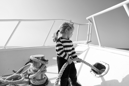 Lets travel around world. Baby boy enjoy vacation cruise ship.Boy adorable sailor shirt yacht travel around world. Child cute sailor help with ropes yacht bow. Adventure boy sailor travelling sea.