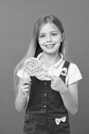 Cute cheerful girl holding giant candy. Imagens