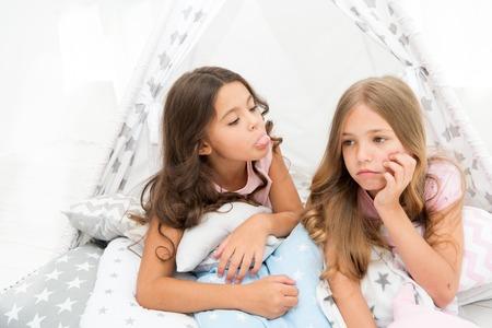 Koncepcja rywalizacji sióstr. Dzieci leżały w domu smutne twarze.