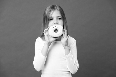 Girl holding big doughnut with icing.