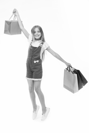 Top tips for smart kid clothes shopping. Girl cute teenager carries shopping bag. 免版税图像