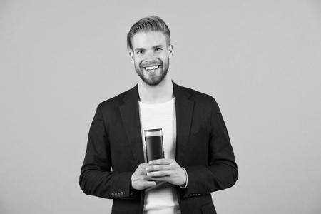 Man stylish hairstyle holds bottle hygienic hair care product grey