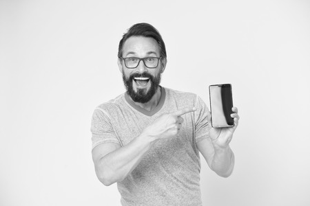 Guy eyeglasses cheerful pointing at smartphone.