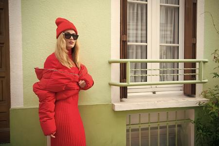 Woman with blonde hair, urban style. Parisian fashion model near house.