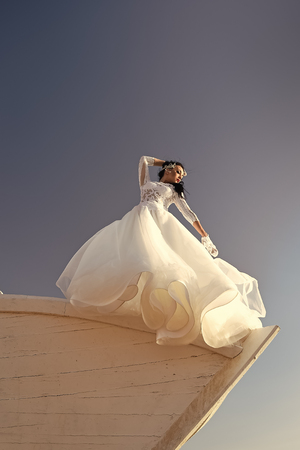 Woman in white dress on boat. Girl in dress on blue sky. Bride and wedding ceremony. Wedding fashion and beauty salon. Elegance and fashion model.
