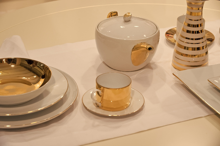 Tea service or set with pot, cup, saucer, plates and vase with golden gilt served on white table cloth background. Tea party or ceremony concept